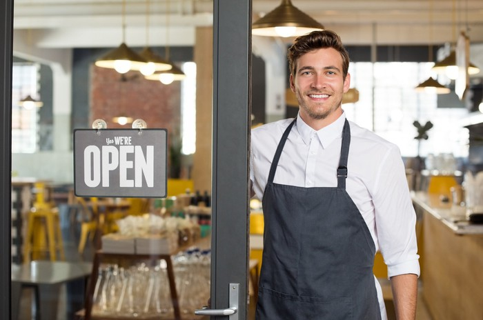 Smiling man in apron standing in restaurant doorway, next to a sign saying Open