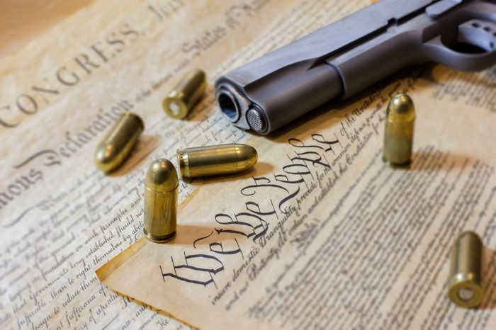 Gun and bullets on a copy of the U.S. Constitution.