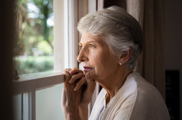 Older woman looking out window