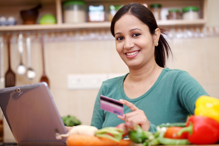 Smiling woman holding a credit card and using a laptop in a kitchen.
