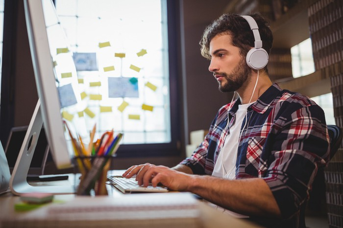 Young man at computer wearing headphones