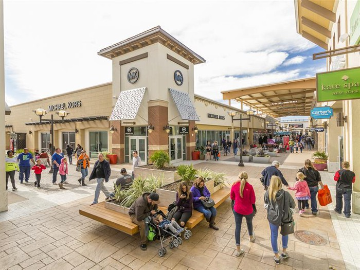 A Tanger outlet center in Fort Worth with several shoppers walking around.