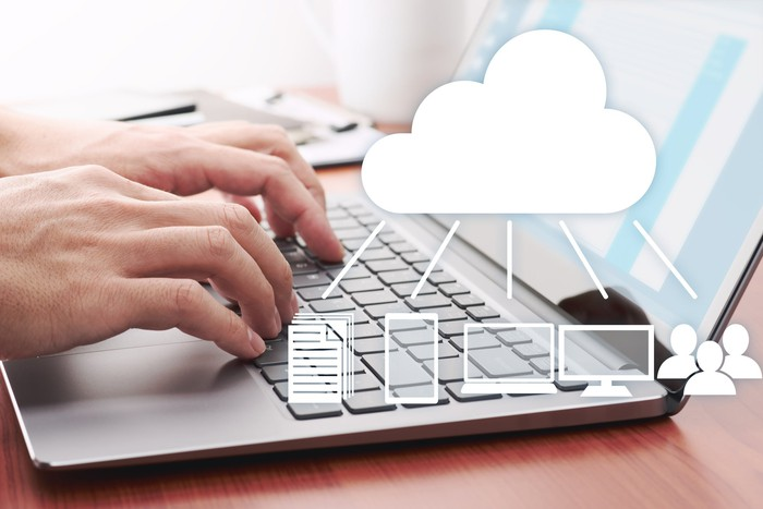 Man using laptop for working with cloud applications.