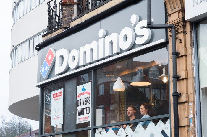 A Domino's storefront with two people looking through the front window.