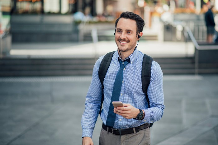 Smiling man outdoors holding cell phone