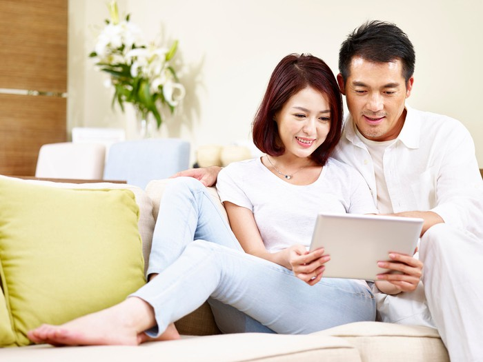 Couple sitting on couch, smiling, while looking at tablet.