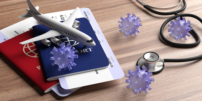 A passport, a model airplane, and a stethoscope on a table top with coronavirus models.