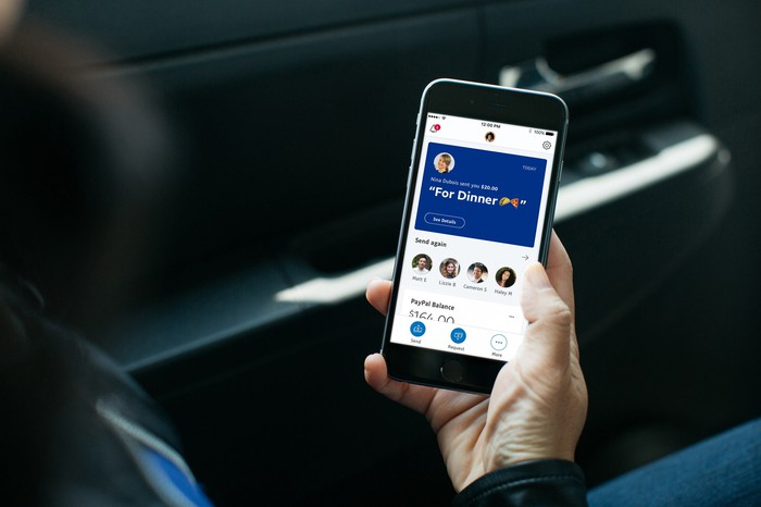 A person sitting in a car holding a smartphone looking at the PayPal app homescreen.