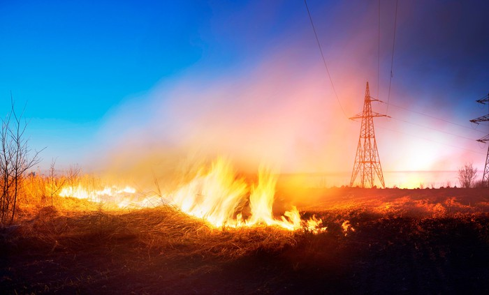 wildfire burning under transmission lines