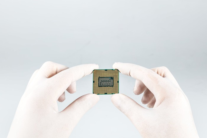 CPU held by the fingertips of someone wearing white rubber gloves.