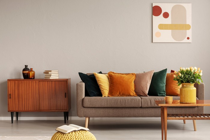 A living room furnished with a couch, coffee table, and sideboard in the midcentury modern style