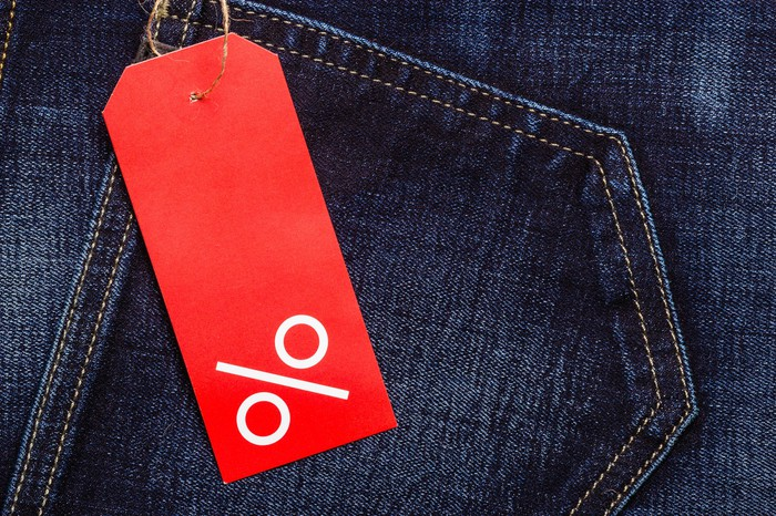 A pair of blue jeans with a red tag featuring a percent sign.