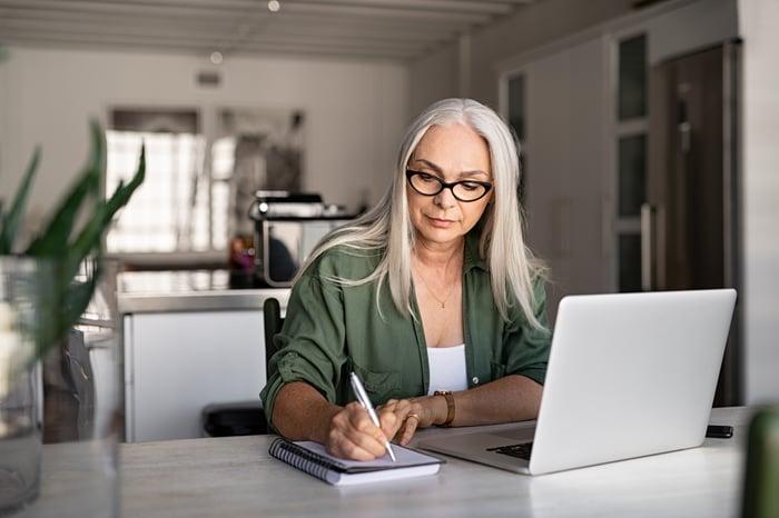 Woman sitting at computer, writing on notepad.