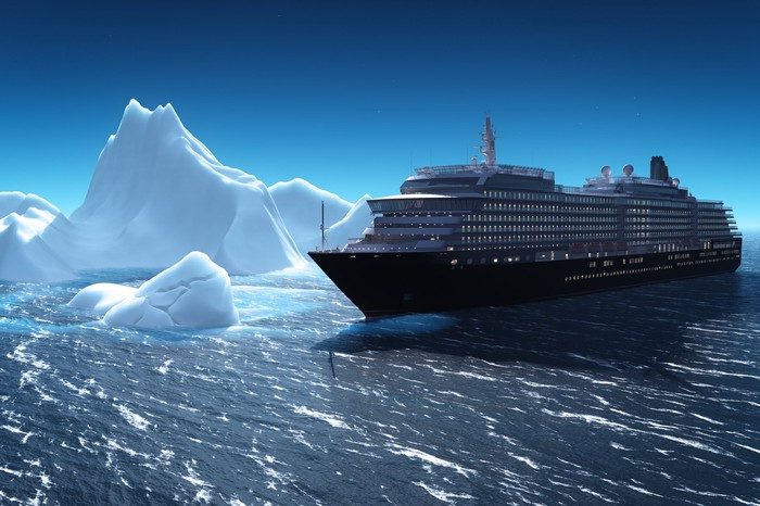 Cruise liner sailing past icebergs