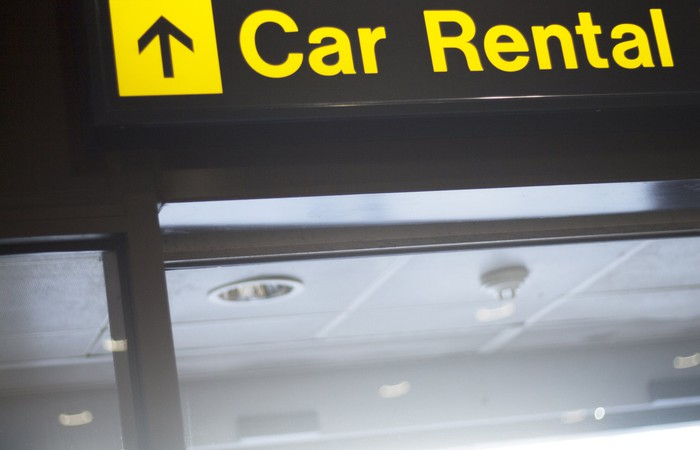 An overhead sign pointing to car rental at an airport.
