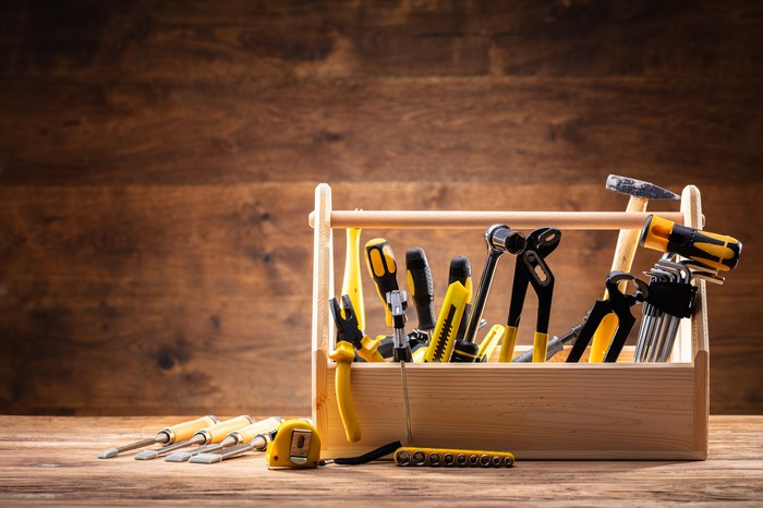 A box of tools, including a hammer, pliers, and a socket wrench.