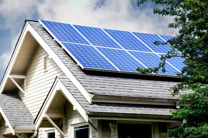 Home with solar panels and cloudy skies in the background.