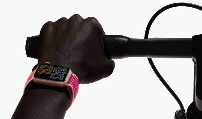 Close-up of hand gripping bicycle handlebar, with a pink Apple Watch around the wearer's wrist