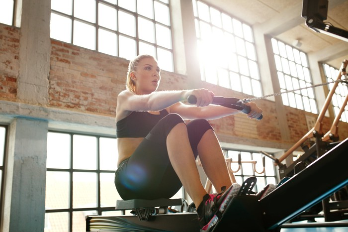 A woman using a rowing machine.