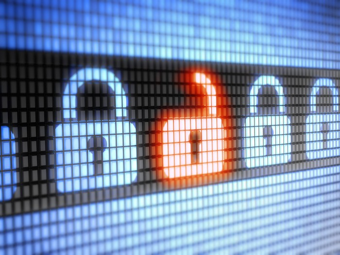 Close-up photo of a computer screen showing a line of blue padlock icons. One red padlock is unlocked.