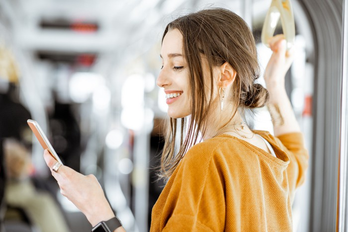 A young woman uses a smartphone while taking a train.