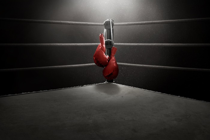 Boxing gloves hang in the middle of a boxing ring.