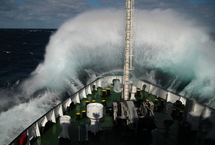 Large wave breaking over bow of ship