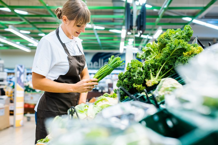 A grocery store employee stocks fresh vegetables.