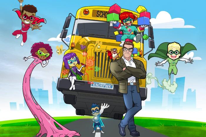 A cartoon still from Stan Lee's Superhero Kindergarten, with kids in superhero capes flying around a school bus