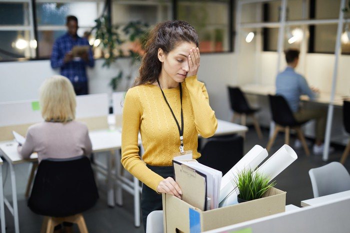 A woman with her hand over her forehead cleaning out her office desk