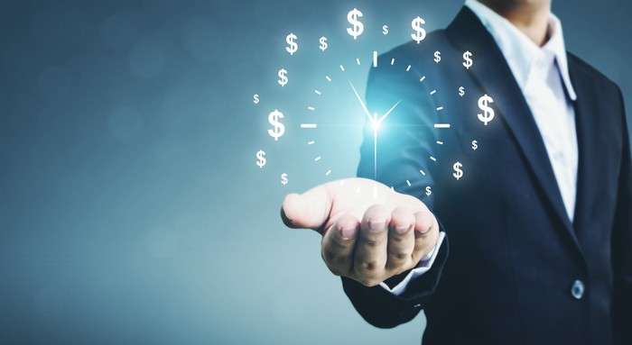 A faceless man with his hand out and illuminated dollar signs and a clock over it.