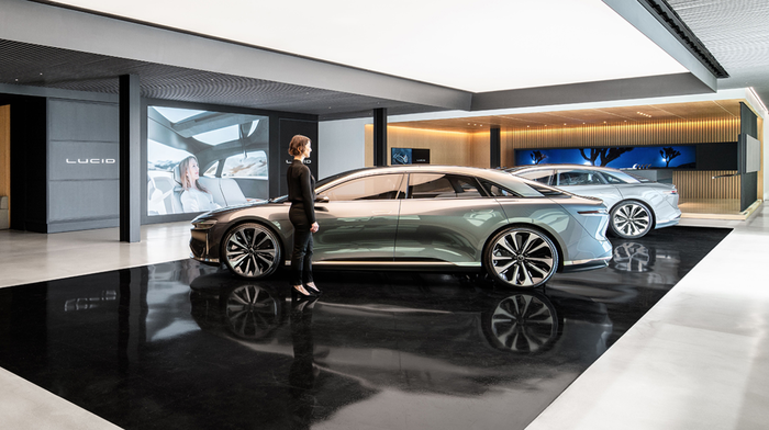 A woman stands in a Lucid showroom.