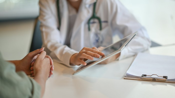 Doctor using a tablet to review information with a patient.