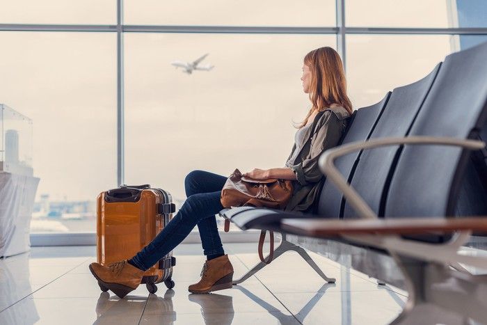Woman seated in airport watching plane through window