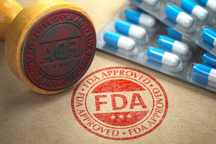 An FDA approval stamp on a desk next to a blister pack of pills.