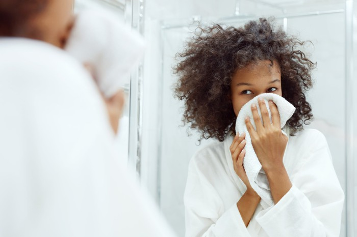 A woman looks in the mirror while she dries her face.