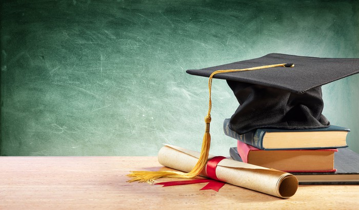 College cap stacked atop books and a rolled up diploma