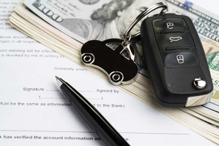 A key fob with a car charm lying atop a pile of cash and auto loan paperwork.