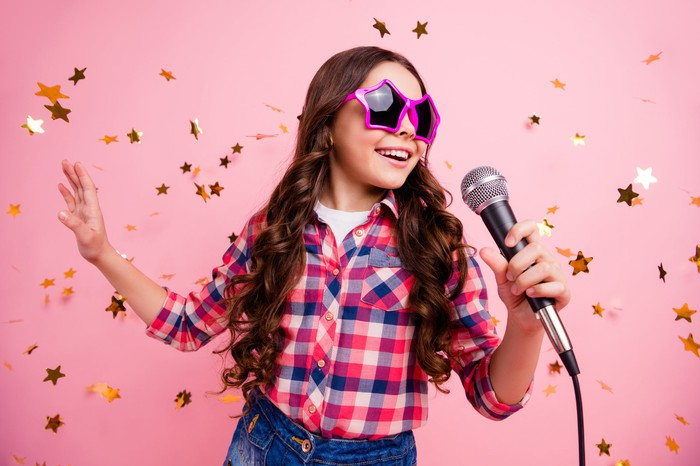 A young girl in star-shaped sunglasses sings a song.