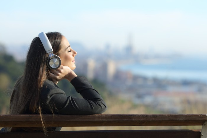 A young woman listens to music on headphones.