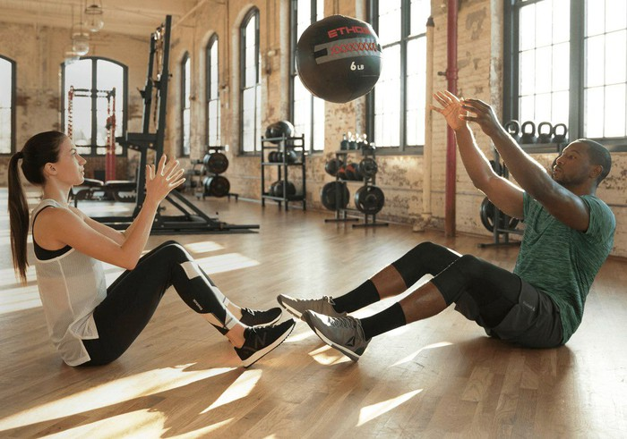 Man and woman throwing a workout ball