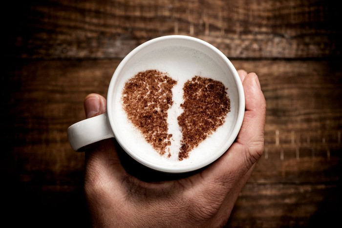 a white ceramic cup of cappuccino, with a broken heart drawn with cocoa powder on its milk foam