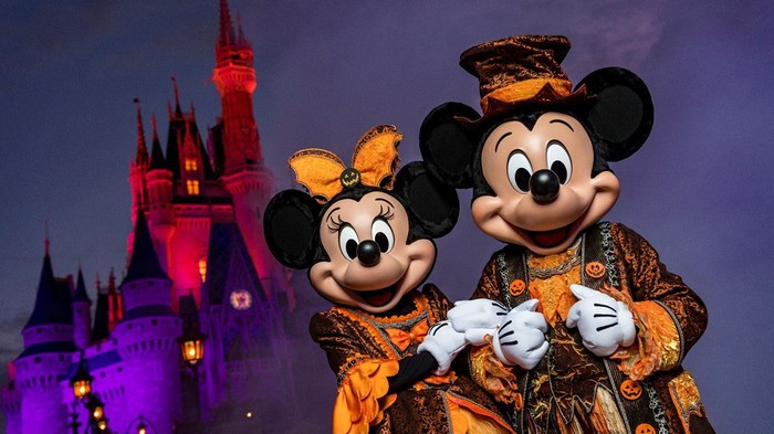 Mickey and Minnie dressed in orange Halloween costumes in front of the Magic Kingdom's castle.