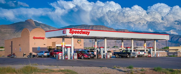 Speedway gas station, with several pumps and cars in the parking lot and a scenic desert mesa background.