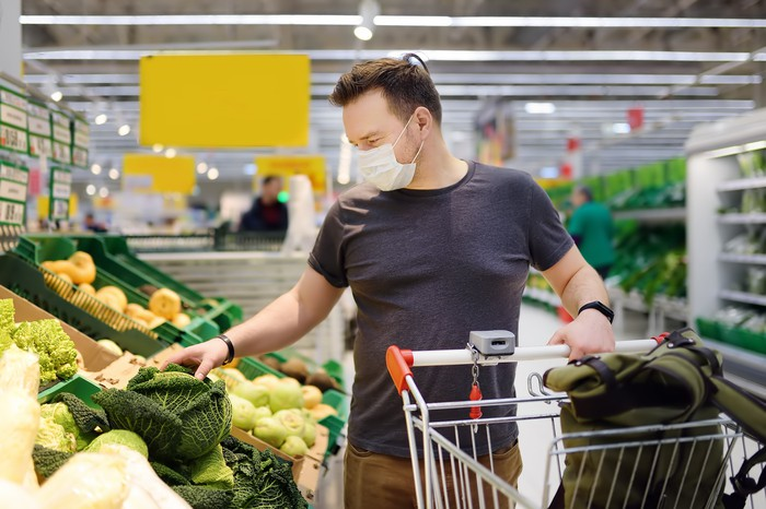 A man wearing a disposable mask shops in the produce section.