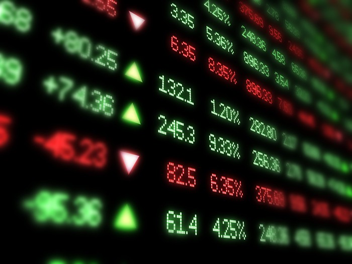 A digital board showing stock prices in green and red.