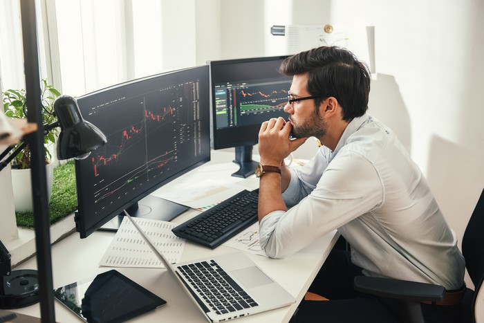 A person looking at a stock chart on a computer screen.