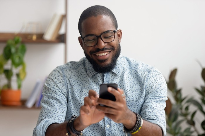 Man smiling while tapping on mobile phone