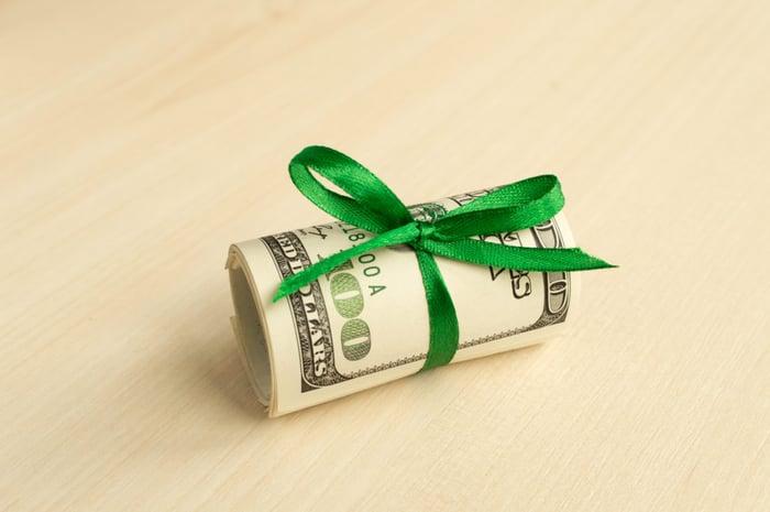 A roll of hunder-dollar bills tied in a green ribbon.