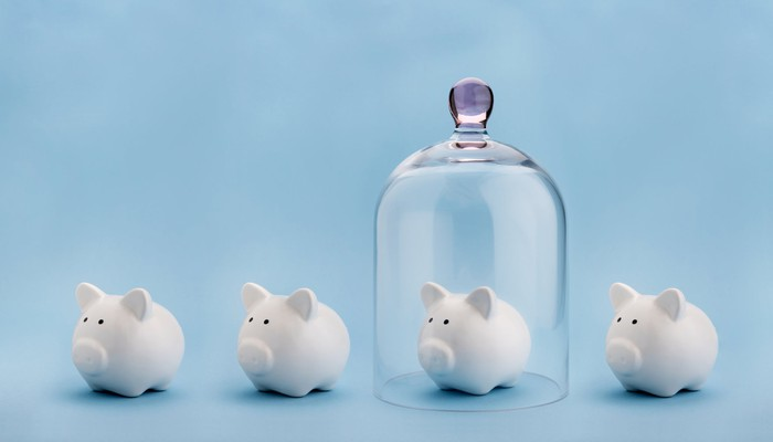 three piggy banks with one covered by a clear upside-down glass jar protecting it.